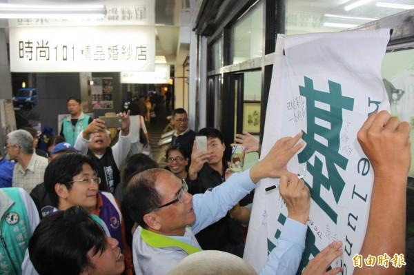 前行政院長游錫堃為「基隆英派青年基地」布條簽名。(記者林欣漢攝)