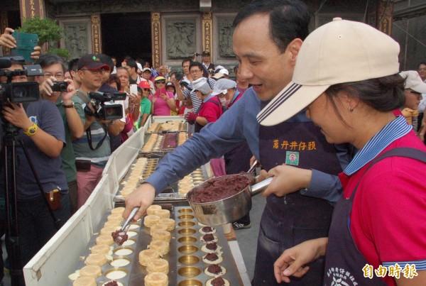 朱立倫試做紅豆餅,被師傅說「餡料不夠滿」。(資料照,記者李立法攝)