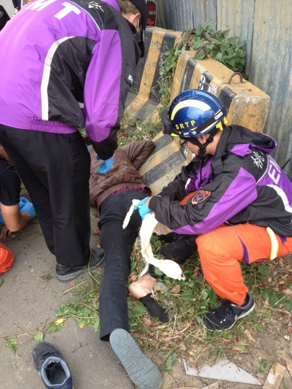 騎士自摔,左小腿插入路邊裸露鋼筋,救護人員到場先行幫騎士包紮傷口後送醫。(記者李容萍翻攝)