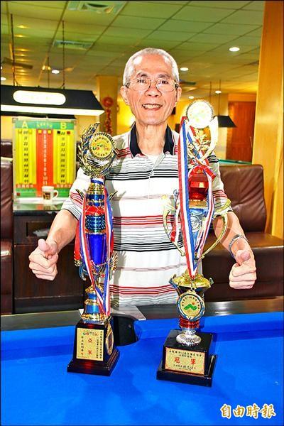 連續2年在縣運撞球賽中稱霸,郭義福開心展示獎盃,還說明年要繼續衛冕。(記者佟振國攝)