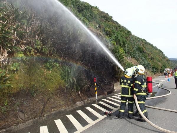 消防人員拉起水線持續降溫,防星火再起。(記者陳賢義翻攝)