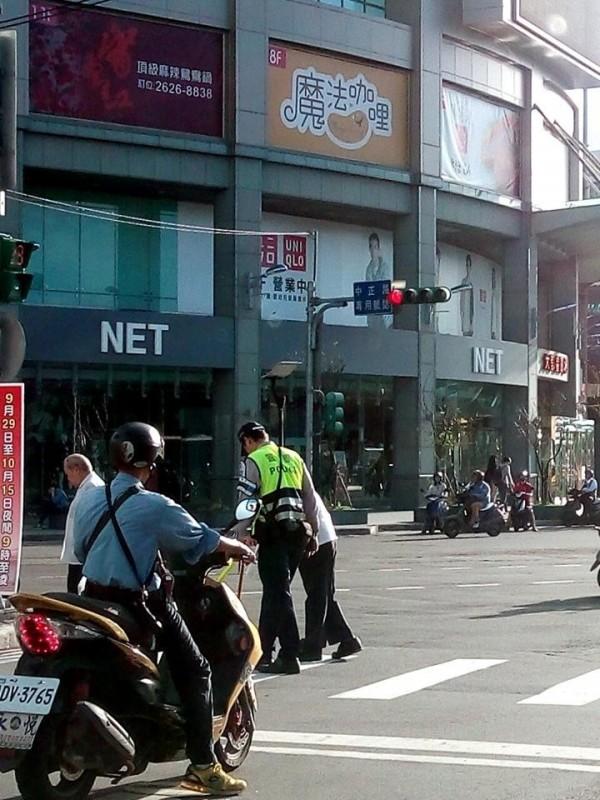 周員護著老翁緩緩通過馬路。(記者黃捷翻攝)