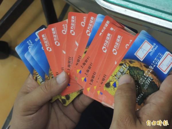 警方在車手身上及車子裡查扣一大疊偽造的銀聯卡。(記者廖淑玲攝)