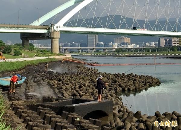 兩名工人今早以強力水柱沖刷基隆河左岸邊受污染的消波塊,一名釣客卻無視周邊情況,繼續垂釣。(記者趙新天攝)