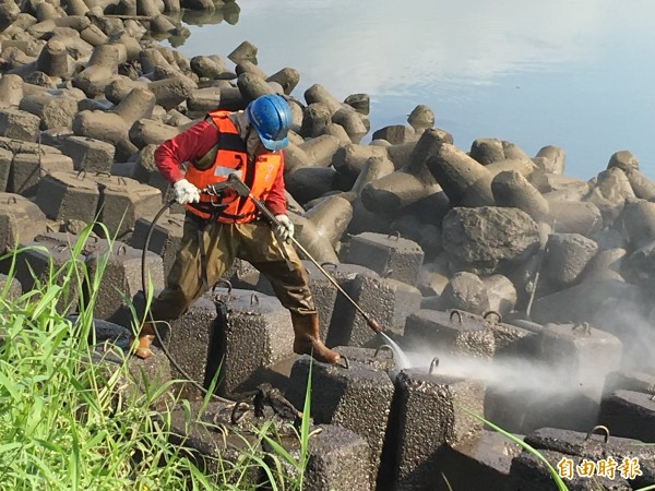 穿著有中油字樣救生背心的工人,以強力水柱沖刷消波塊,但沖下去的污油有二次污染的可能。(記者趙新天攝)
