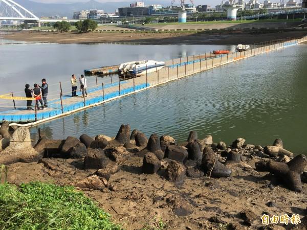 中油公司在麥帥一橋下搭起浮橋,還停了兩艘快艇,工作人員相互討論,旁邊消波塊上油污明顯未除。(記者趙新天攝)