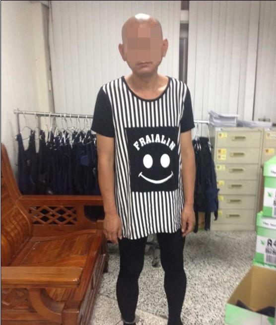 頂著大光頭的張嫌穿著時下流行的女裝「長版衣搭褲襪」,要警方不注意也難。(記者許國楨翻攝)