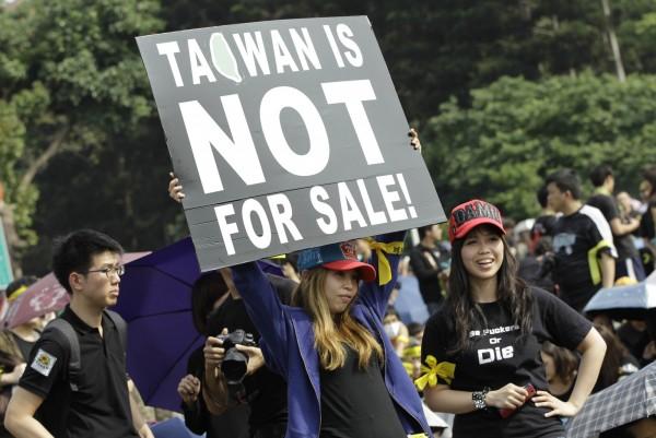 年輕世代(20-29歲)高達98%認同自己是台灣人,並有81.9%認同台灣未來應獨立成一個國家。圖為馬習會時,年輕學子高舉抗議看板。(資料照,美聯社)