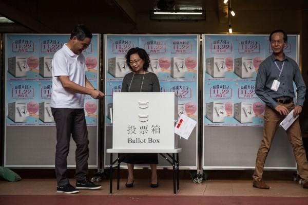 香港今日舉行區議會選舉,香港特首梁振英(左)親自投票。(法新社)