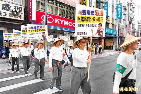 民眾手持看板沿街遊行,高喊「保障國會品質,失能立委去職」。(記者張安蕎攝)