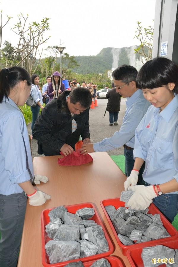 民眾用紅布將貫通石包起,準備拿到廟宇過爐。(記者朱則瑋攝)