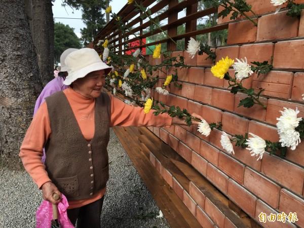 在公共藝術「靜默之聲」置放菊花,悼念受難者英靈。(記者林孟婷攝)