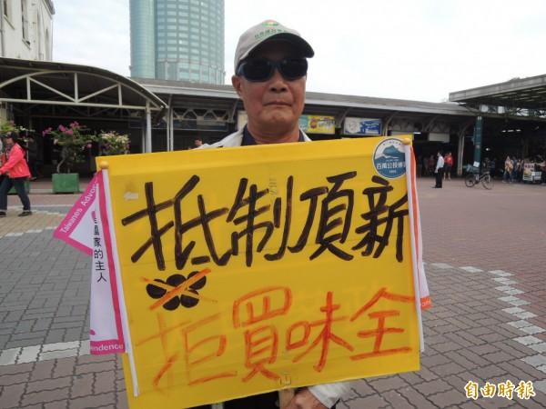 王溪河在台南火車站舉牌抗議,並發起「抵制頂新、拒買味全」舉牌抗議行動。(記者蔡文居攝)