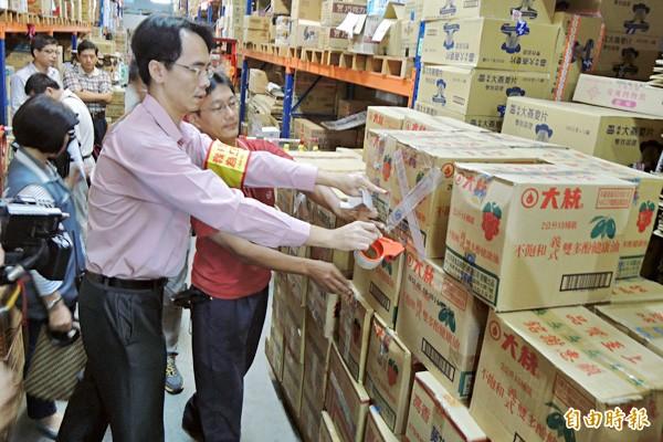 2013年爆發大統的葡萄籽油摻混銅葉綠素,台糖量販店人員將倉庫裡下架的大統公司油品貼上封條。(資料照,記者劉婉君攝)
