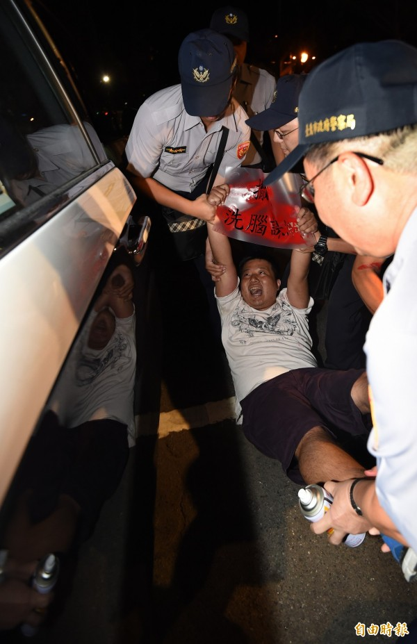 抗議學生遭警方押進警車送離。(資料照,記者簡榮豐攝)