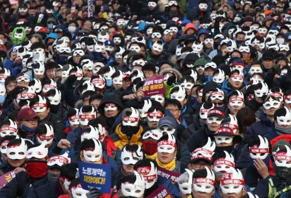 大批農人、工人上街抗議,頭戴白色面具並高舉標語「朴槿惠下台」。(美聯社)