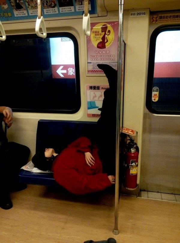 一名捷運乘客竟然橫躺博愛座並把雙腳抬放在塑膠板上,呈現彎曲90度的L型坐姿,完全無視旁人眼光。(圖擷自爆料公社)