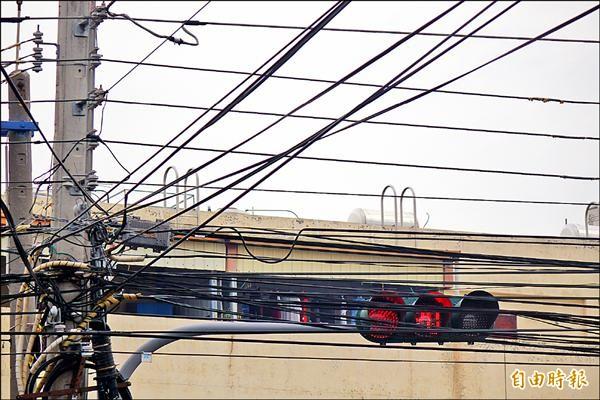彰化縣和美鎮嘉犁派出所前的紅綠燈,快要被密密麻麻的電線給「遮住」了!(記者劉曉欣攝)