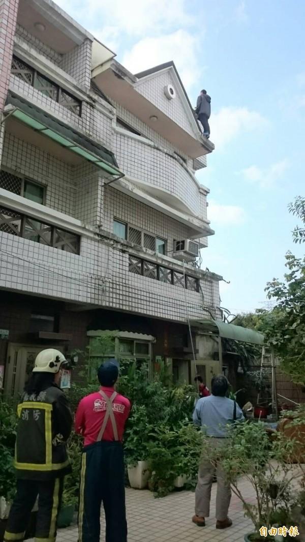 李男站在自家樓頂要輕生,消防隊全員做好救援措施。(記者余雪蘭攝)