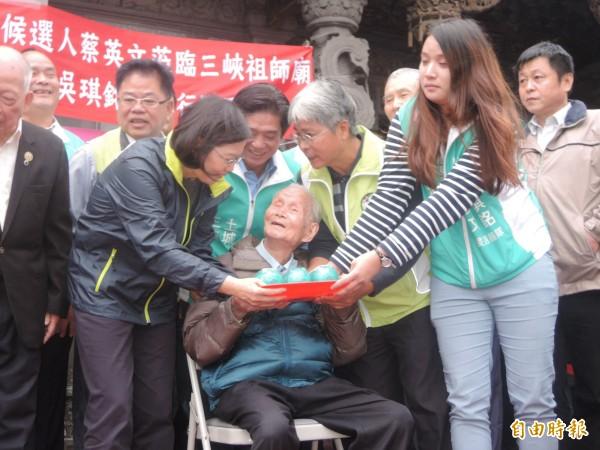 三峽108歲人瑞林(上不下直)送給蔡英文三隻小豬撲滿。(記者翁聿煌攝)