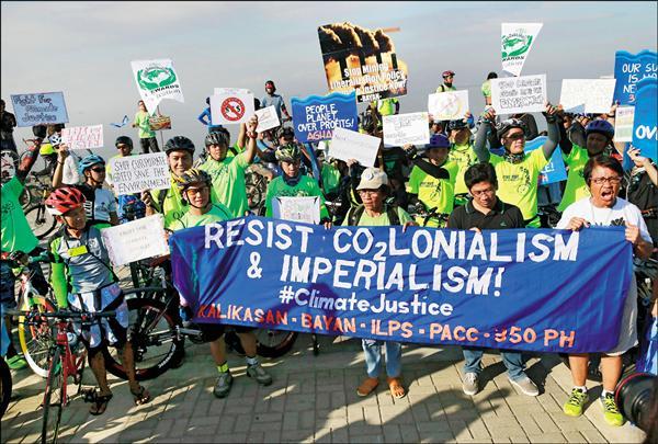 菲律賓環保人士十三日騎單車在馬尼拉參加對抗氣候變遷示威,要求環境正義。(路透)