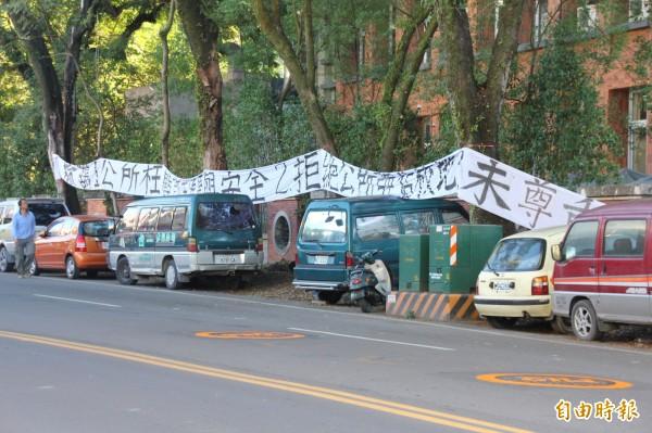 埔里高工學生不滿公所在校牆外道路用地規劃大、小型車輛停車格,日前掛出白布條抗議。(記者佟振國攝)