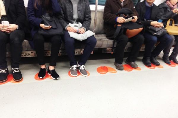 南韓地鐵為了對付「腿開開」的乘客,推出「LOUD」計畫,在每個座位的地上貼上橙色的愛心,提醒乘客將腳放在愛心內。(圖取自《서울시(Seoul)臉書》)