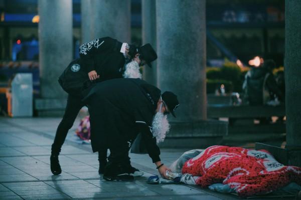 他們會低調、以不打擾街友的方式,分送物資給在寒冬中打地鋪的街友們。(圖擷自「黑色聖誕老人.BLACK SANTA」臉書)