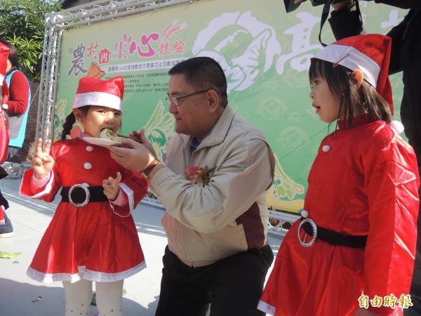 雲林縣農會總幹事簡明欽(中)餵小朋友吃高麗菜。(記者廖淑玲攝)