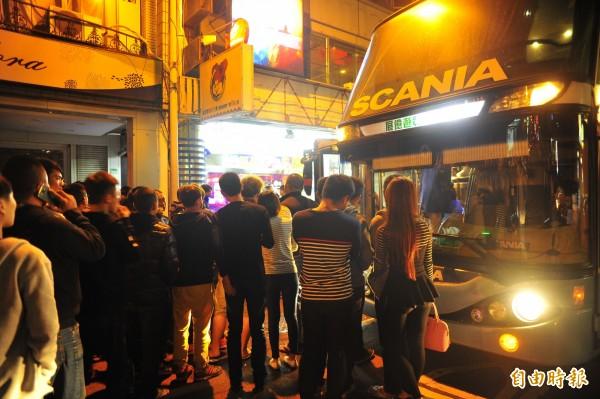 警方大動作包遊覽車載嫌犯,引起路邊民眾圍觀。(記者王捷攝)