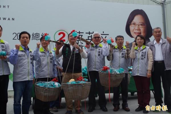李進勇(右4)擔起裝滿小豬的擔子,承擔人民的托負,點亮台灣未來。(記者林國賢攝)