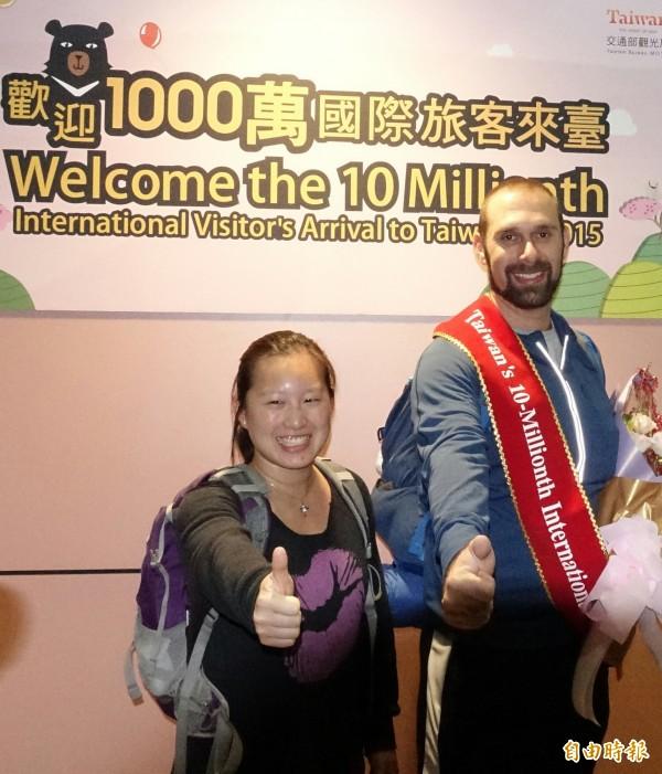 今年第1千萬名來台旅客於清晨5點38分在桃園機場誕生,34歲來自美國的旅客Christopher(左右)成為第1千萬名來台旅客,他是第1次來台灣,與他同行的是台裔美籍的太太Tina,他用手勢比出對他來說真是好大的驚喜。(記者姚介修攝)