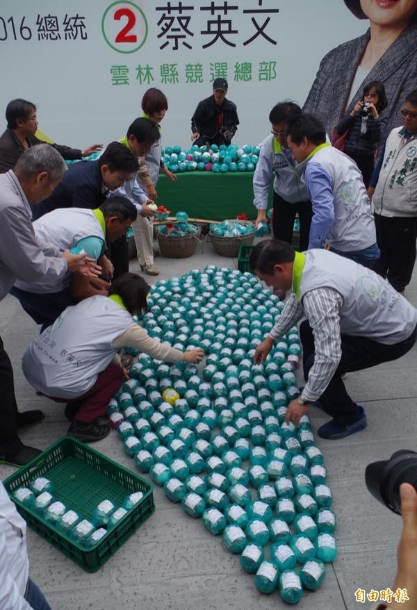 工作人員用小豬排出小豬圖像,象徵人民的力量點亮台灣。(記者林國賢攝)