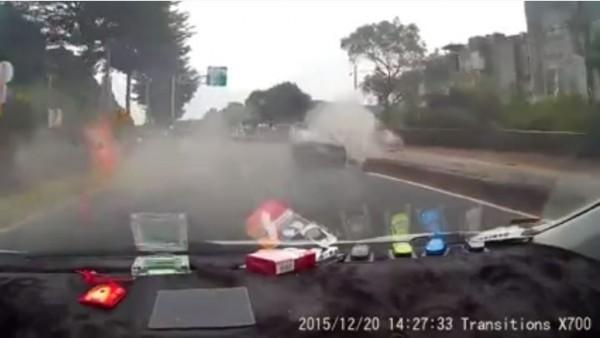 影片中黑色轎車在路口過彎無法拉回車頭自撞分隔島,但這段影片中「對話效果」卻比畫面更精彩。(圖擷取自臉書粉絲專頁「檢舉達人-路安專案」)