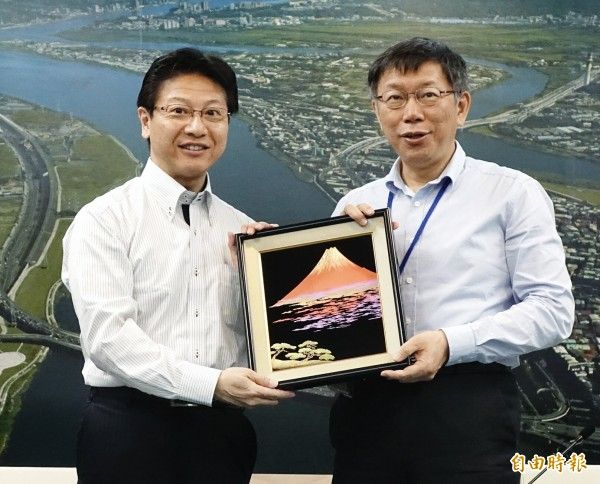 日本靜岡市長田邊信宏(左)今天拜會台北市長柯文哲,互贈紀念品,田邊信宏還特地配合柯P穿著,也將西裝外套和領帶脫掉。(記者方賓照攝)