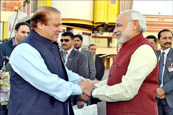 印度總理莫迪(右)廿五日意外造訪巴基斯坦,並與巴國總理夏瑞夫(左)會面,雙方針對包括喀什米爾等雙邊議題交換意見。(法新社)