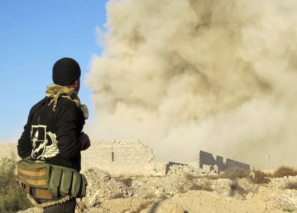 一名伊拉克親政府部隊的成員27日在政府軍清剿佔領拉馬迪的伊斯蘭國好戰份子時,看著拉馬迪冒出陣陣煙塵。(法新社)