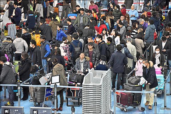 日本進入年假出國旅遊高峰期,東京羽田機場人潮湧現。日媒報導,台灣、夏威夷及關島是日人旅遊勝地。(法新社)