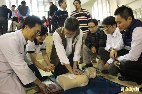 醫師和醫護人員從旁指導縣府人員學習新版CPR,牢記口訣「叫叫CABD」。(記者張聰秋攝)