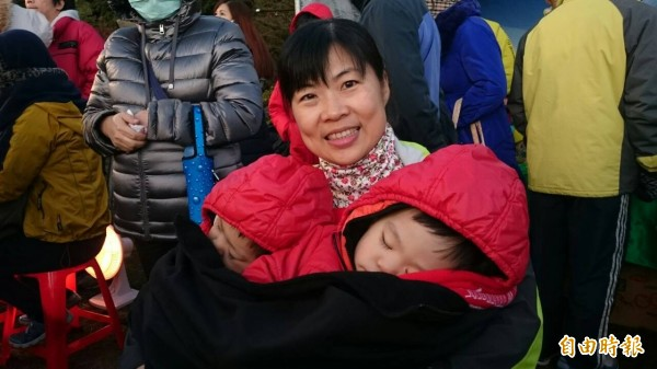 李太太帶著一對雙胞胎到阿里山看日出,小朋友在等待中睡在母親的懷抱。(記者余雪蘭攝)