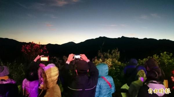 在阿里山對高岳平台看日出的民眾,拿著手機對著高山守候。(記者余雪蘭攝)