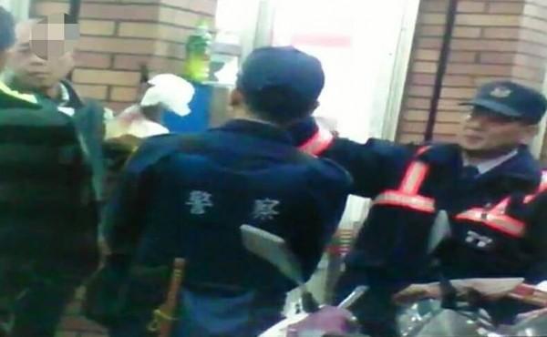 蔡姓男子(左後)持刀與警方對峙,警方趁著拿衛生紙給他擤鼻涕時將其制伏。(記者余雪蘭翻攝)