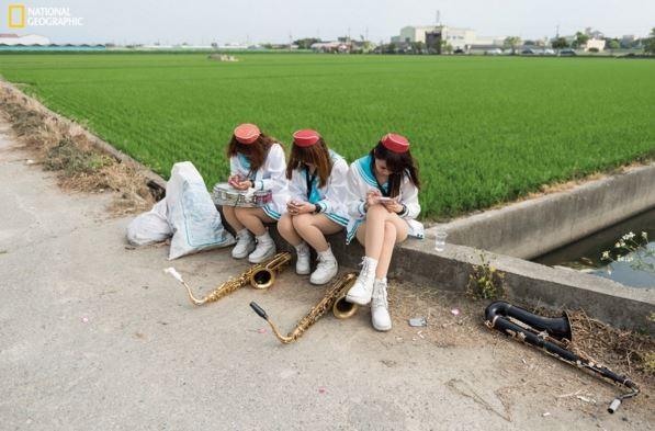 德國籍攝影師胡布納( Lars Hübner) 拍攝關於台灣的系列作品「無可奉告」(Nothing to Declare)中,以一張雲林斗六鄉間出殯隊伍於田邊休息的照片,獲得「人物組」優等獎。(圖擷取自《國家地理雜誌》網站)