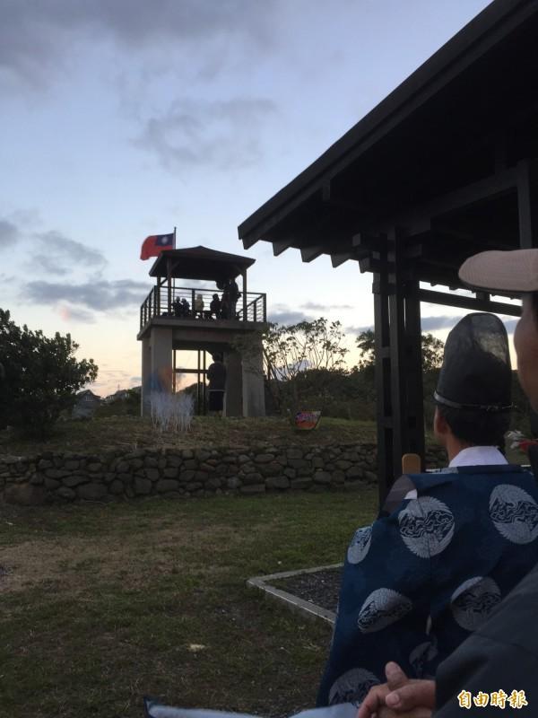 佐藤停下手邊工作隨著村民目視著國旗。(記者蔡宗憲攝)