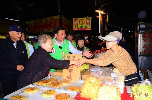 台北市長科文哲的雙親柯承發(左1)與何瑞英(左2)陪同王定宇拜票,受到攤商熱情歡迎。(記者吳俊鋒攝)
