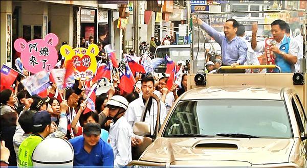 朱立倫(左)、吳育仁掃街車隊行經嘉義市區,有支持者舉牌寫著「嘉義阿嬤」,獻花給朱立倫。(記者王善嬿翻攝)
