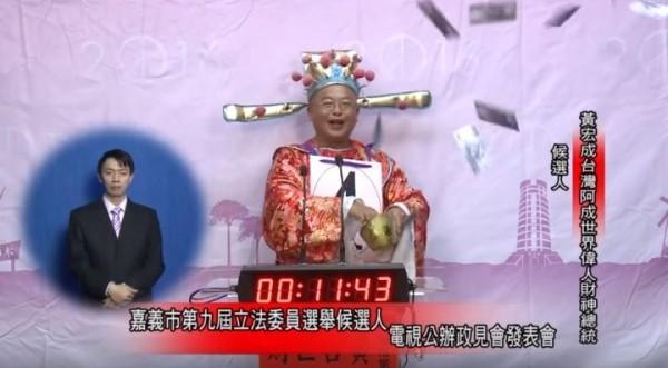 阿成在政見發表時,唱新年歌灑假鈔票。(圖擷取自影片)