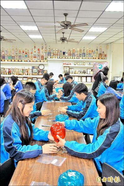 各班學生代表殺小豬,將錢幣計算好後放入袋中。(記者李忠憲攝)