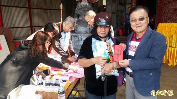 新營三聖宮主委盧振華(右)發過年紅包和1包白米給弱勢戶。(記者楊金城攝)