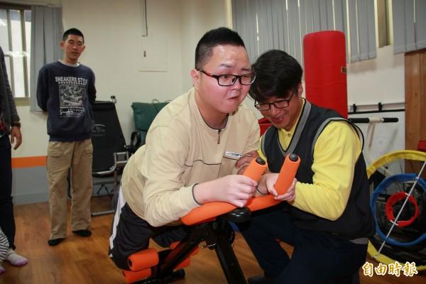 小丑魚製衣公司總經理謝宏昌(右一)協助身障學員使用器材。(記者陳文嬋攝)
